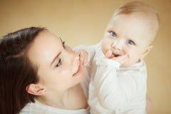 La mère regarde l'enfant avec amour de soin, bébé sur des bras Photos stock