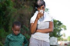 La mère regarde le téléphone tandis que son fils joue près de elle images libres de droits