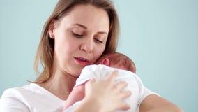 La mère se trouve sur l'épaule du bébé nouveau-né et sourit tendrement Santé nouveau-née, rotant Neonatologist clips vidéos