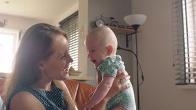 La mère supporte son bébé de sourire adorable s'asseyant sur le sofa 4K Photo libre de droits
