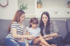 La mère, la tante et l'enfant ayant le temps lerning ensemble avec utiliser le comprimé à la maison avec détendent et heureux sur Photographie stock libre de droits