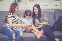 La mère, la tante et l'enfant ayant le temps lerning ensemble avec utiliser le comprimé à la maison avec détendent et heureux sur Images stock