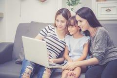 La mère, la tante et l'enfant ayant le temps lerning ensemble avec utiliser l'ordinateur portable à la maison avec détendent et h Photos stock