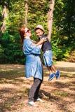 La mère tient et soulève son fils pour l'amusement en parc photos libres de droits