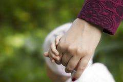 La mère tient la main de l'enfant Photo stock