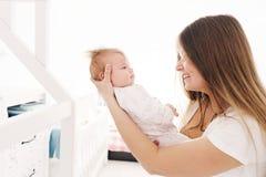 La mère tient son fils nouveau-né dans la lumière arrière Famille et concept de sécurité photos stock