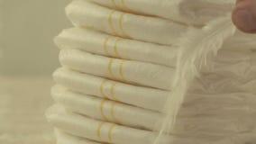 La mère tient une plume légère blanche sur des couches-culottes de bébé, le concept de la légèreté et le confort, le plan rapproc banque de vidéos