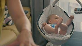 La mère travaille à la maison pendant les mensonges de bébé dans le berceau banque de vidéos