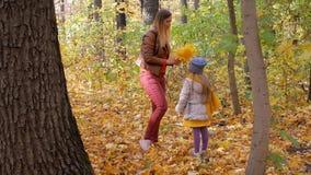 La mère tricote la guirlande jaune de feuille ainsi que l'enfant banque de vidéos