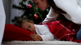 La mère vient et les couvertures dort sur le bébé de plancher avec un plaid rouge au réveillon de Noël banque de vidéos