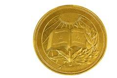 La médaille avec l'image du livre et un laurier s'embranchent sur un fond blanc. Photo stock