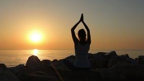 La méditation de matin, femme pratique le yoga sur le bord de la mer, tir sur la marque IV d'EOS 5D de Canon dans le mouvement le banque de vidéos