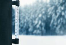 La météorologie, les prévisions et l'hiver survivent au concept de saison - thermomètre sur un vitrail avec le fond neigeux de fo Photographie stock libre de droits
