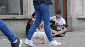 La música de la calle, par de guitarristas juega y canta en la calle que se sienta en el asfalto entre transeúntes almacen de video