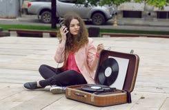La música envició a la muchacha que se divertía con auriculares y un sistema estéreo portátil del disco de vinilo Imagen de archivo libre de regalías