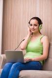 La música que escucha de la chica joven en casa Imágenes de archivo libres de regalías