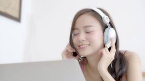 La música que escucha del auricular feliz asiático hermoso de la mujer con se relaja y goza en el dormitorio