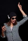 La música que escucha feliz con los auriculares grandes llama por teléfono o jugador Imagen de archivo libre de regalías