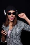 La música que escucha feliz con los auriculares grandes llama por teléfono o jugador Imagen de archivo