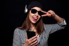 La música que escucha feliz con los auriculares grandes llama por teléfono o jugador Fotos de archivo