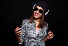 La música que escucha feliz con los auriculares grandes llama por teléfono o jugador Foto de archivo