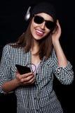 La música que escucha feliz con los auriculares grandes llama por teléfono o jugador Fotos de archivo libres de regalías
