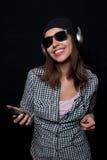 La música que escucha feliz con los auriculares grandes llama por teléfono o jugador Imagenes de archivo