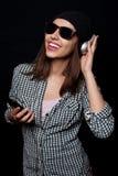 La música que escucha feliz con los auriculares grandes llama por teléfono o jugador Imágenes de archivo libres de regalías
