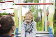 La m?re attrape la fille de l'des enfants glissent, fille satisfaisante satisfait sur un terrain de jeu d'enfants images stock