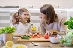 La m?re et la fille faisant cuire ensemble dans la salade, le parent et l'enfant v?g?taux de cuisine parlent le sourire photo stock