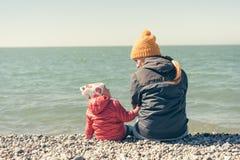 La m?re et la fille s'asseyent sur la plage image stock