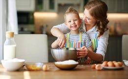 La m?re et le fils heureux de famille font la p?te cuire au four de malaxage dans la cuisine image stock