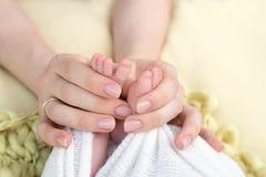 La m?re tient les pieds du b?b? nouveau-n? avec ses mains, doigts sur le pied, soin maternel, amour et ?treintes de famille, tend photographie stock libre de droits