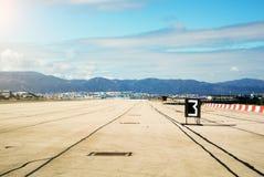 La mañana con abajo asolea luces en la pista del aeropuerto de Gibraltar, de montañas y del puerto de Algeciras Imágenes de archivo libres de regalías