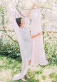 La mañana de la novia hermosa Ella está sosteniendo el vestido de boda Foto de archivo