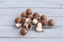 La macadamia es una nuez australiana, un Kindal En un mando de madera es un color gris-azul Imagen de archivo