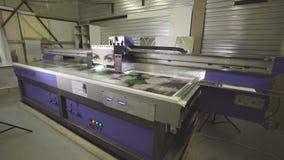 La macchina applica rapidamente il disegno alla tela sulla stampante stock footage
