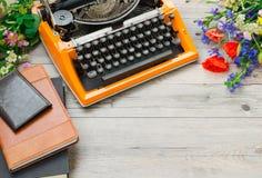 La macchina da scrivere d'annata arancio con un mazzo del campo dell'estate fiorisce Fotografia Stock