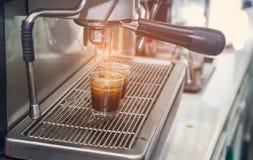 La macchina del caffè del caffè espresso con il filtro produce il caffè che sfocia nella corrente alternata Fotografie Stock