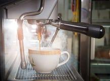La macchina del caffè del colpo del caffè espresso con il filtro produce il caffè int scorrente Immagini Stock