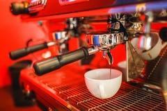 La macchina del caffè produce a due il caffè su fondo rosso Fotografia Stock Libera da Diritti