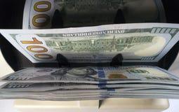 La macchina del contatore dei soldi elettronici sta contando sta contando le banconote americane dei dollari americani del cento- fotografia stock
