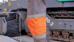 La macchina del lastricatore dell'asfalto durante la costruzione di strade, squadra della costruzione di strade applica lo strato stock footage
