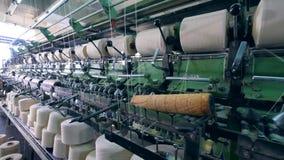 La macchina della fabbrica dell'indumento sta avvolgendo i fili Attrezzatura della fabbrica del tessuto archivi video