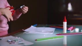 La macchina fotografica che fa scorrere a sinistra sulle mani del bambino della bambina in carta rosa di taglio del maglione mode archivi video