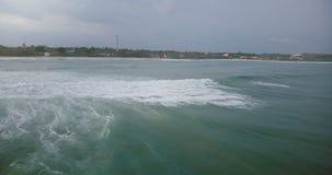 La macchina fotografica del fuco gira a sinistra per seguire l'onda di oceano enorme che raggiunge la spiaggia tropicale pacifica archivi video