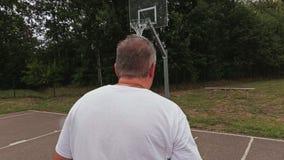 La macchina fotografica del primo piano segue il giocatore di pallacanestro stock footage