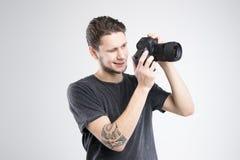 La macchina fotografica della tenuta del giovane in camicia nera ha isolato lo studio Immagine Stock