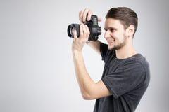La macchina fotografica della tenuta del giovane in camicia nera ha isolato lo studio Fotografia Stock