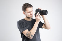 La macchina fotografica della tenuta del giovane in camicia nera ha isolato lo studio Immagini Stock